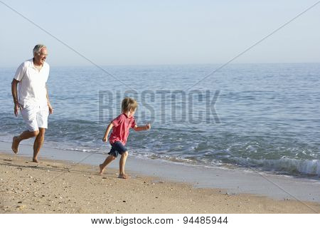 Grandfather And Grandson Running Along Beach