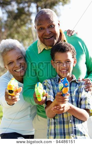 Grandparents And Grandson Shooting Water Pistols