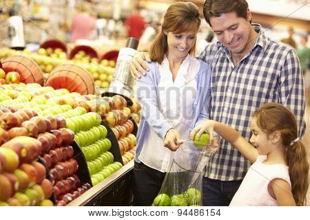 Family buying fruit in supermarket