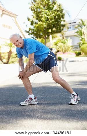 Elderly man warming up for run