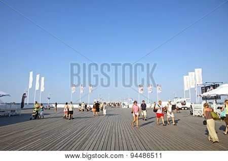 Tourists Walking Along The Wooden Pier In Sopot, Poland