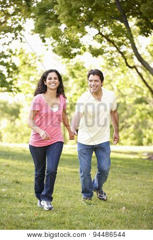 Young Hispanic Couple Running In Park