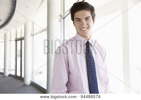 Portrait Of Young Businessman Standing In Corridor Of Modern Office Building
