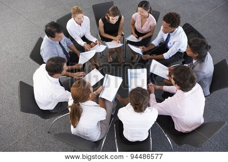 Overhead View Of Businesspeople Seated In Circle At Company Seminar