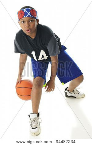 Full length image of a preteen basketball player looking at the viewer as he dribbles between his legs.  On a white background.