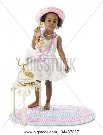 An adorable 2 year old diva calling the viewer to her fancy French phone.  She wears a white slip and petticoat, and pastel hat and beads.  On a white background.