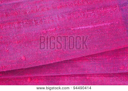 Red silk fabric folded background and texture