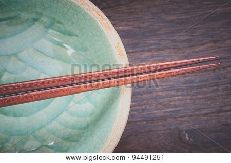 Wood brown chopsticks and celadon green ceramic on wood table background