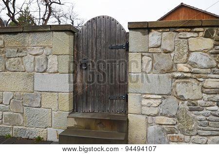 The stone fence with wooden gate on Mtskheta street. Georgia