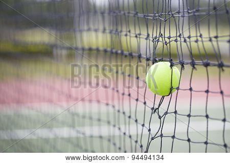 Tennis Ball In Net At Tennis Court