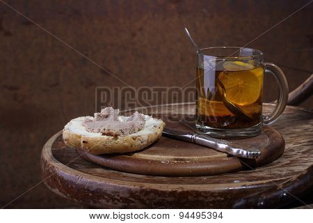 Sandwich With Meat Paste And Tea With A Lemon In A Transparent Mug On A Wooden Table