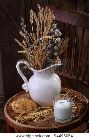 Light Morning Meal With Milk And Fresh Bread And A Bouquet From Cones And A Willow
