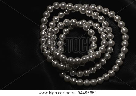 White Pearl Necklace On A Black Silk