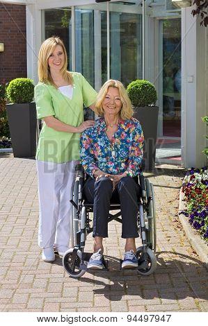 Portrait Of Nurse With Senior Woman In Wheelchair