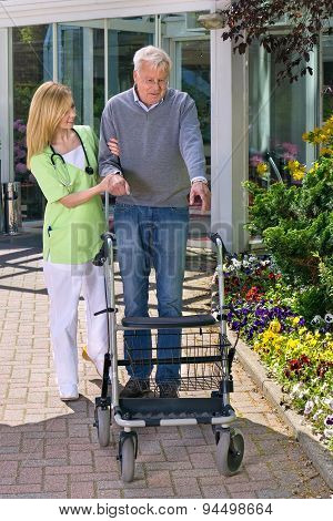 Nurse Helping Senior Man With Walker Outdoors