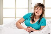 stock photo of early morning  - middle age woman laying in bedroom at early morning - JPG