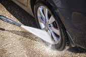 stock photo of pressure-wash  - High pressure manual car washing outdoors - JPG