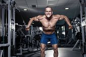 stock photo of abdominal muscle  - Muscular bodybuilder guy doing exercises workout in gym  - JPG