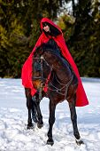 foto of cloak  - beautiful woman with red cloak with horse outdoor in winter - JPG
