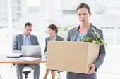 stock photo of forlorn  - Businesswoman leaving office after being fired and carrying her belongings - JPG