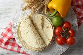 foto of whole-wheat  - Stack of homemade whole wheat flour tortilla and vegetables on cutting board - JPG