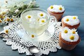 foto of chamomile  - Cup of chamomile tea with chamomile flowers and tasty muffins on color wooden background - JPG