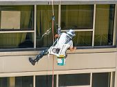 stock photo of window washing  - Professional window washer cleaning windows on a building - JPG