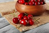 pic of sackcloth  - Fresh cherries in bowl with sackcloth on wooden table - JPG