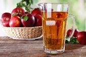 image of jug  - Full jug of apple juice and fruits on bright background - JPG