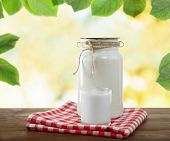 pic of milk glass  - Retro can for milk and glass of milk on wooden table - JPG