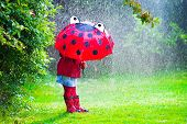 stock photo of boot  - Little girl with red umbrella playing in the rain - JPG
