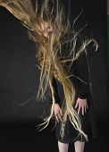 picture of hair blowing  - Mysterious Looking Blond Woman Wearing Black Dress Standing in Studio with Black Background with Long Hair Blowing in Strong Wind - JPG