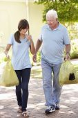 stock photo of grandfather  - Teenage Granddaughter Helping Grandfather With Shopping - JPG