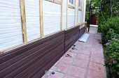 pic of soffit  - Installation of brown plastic siding on the facade of the house - JPG