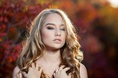 image of chest hair  - young woman on a background of red and yellow autumn leaves with beautiful curly hair on his chest - JPG