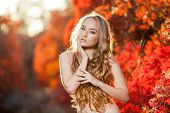 stock photo of chest hair  - young woman on a background of red and yellow autumn leaves with beautiful curly hair on his chest - JPG