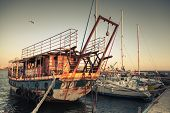 stock photo of old boat  - Old rusted pleasure boat is moored in Nesebar ancient historical town Bulgaria - JPG