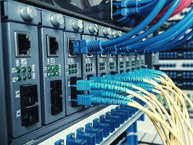 stock photo of cat5  - Fiber Optic cables connected to an optic ports and UTP Network cables connected to ethernet ports - JPG