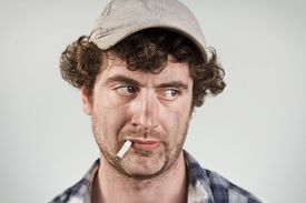 stock photo of disapproval  - Disapproving redneck glances over his shoulder while smoking his cigarette - JPG