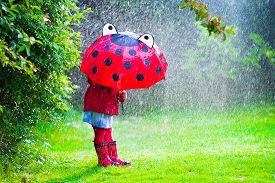 stock photo of rainy season  - Little girl with red umbrella playing in the rain - JPG