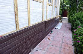 stock photo of soffit  - Installation of brown plastic siding on the facade of the house - JPG