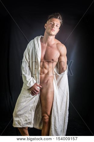 Handsome totally naked young man wearing white bathrobe, isolated on black background