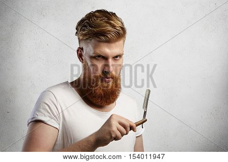 Fashionable Redhead Barber With Stylish Haircut And Fuzzy Beard Holding Cut-throat Razor In His Hand