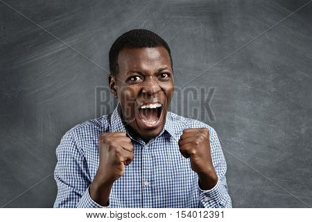 Isolated Portrait Of Young Angry African Man In Blue Shirt Clenching His Fists, Screaming With Anger