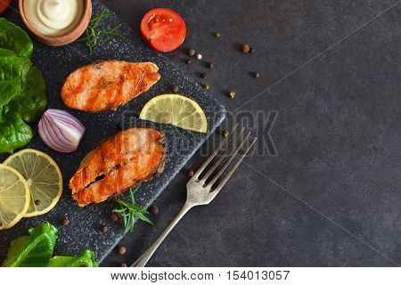 Salmon steak grilled with peppers and lemon on a black background.