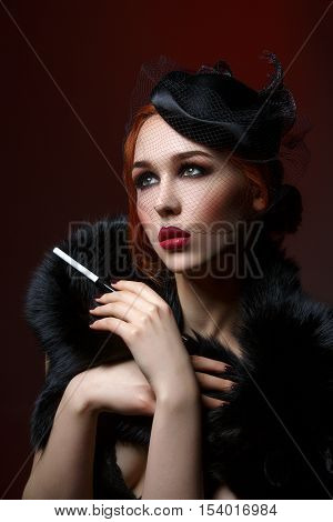 Beautiful young woman with smoky eyes and full red lips holding cigarette holder. Vintage head piece. Retro styling. Studio beauty shot. Copy space.