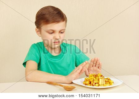 Little boy does not want to eat a fries