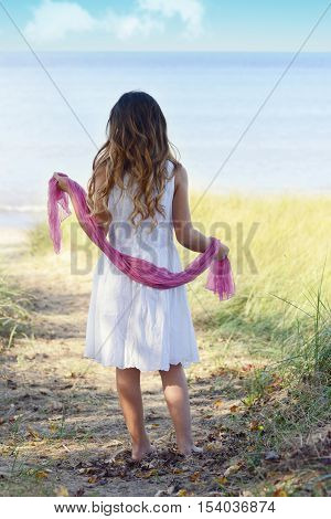 little girl at beach with pink scarf