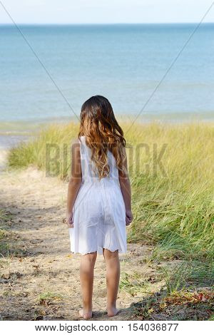 little girl at the ocean walking on a path