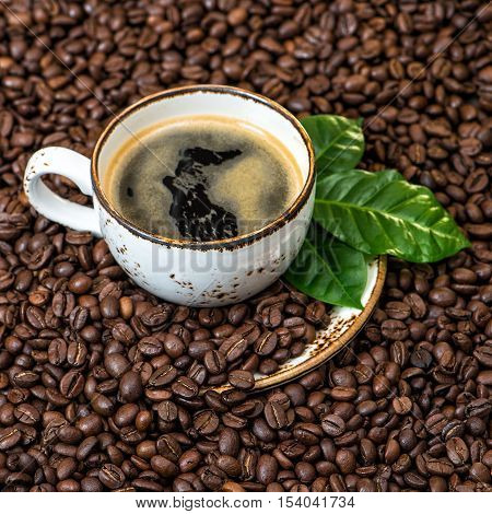 Black coffee with green leaves on coffee beans background square